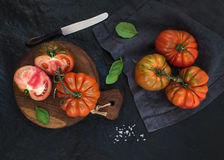 Fresh ripe hairloom tomatoes and basil leaves on rustic wooden board over black stone background, horizontal Stock Photo