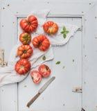 Fresh ripe hairloom tomatoes and basil on rustuc Royalty Free Stock Photo