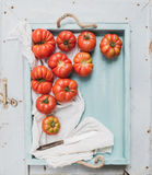 Fresh ripe hairloom tomatoes in rustuc blue wooden tray Royalty Free Stock Photography
