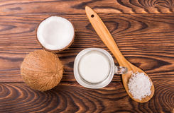 Fresh, ripe half cut coconut with a glass of milk and wooden spoon with coco chips on a wooden background. Ripe half cut coconuts. Royalty Free Stock Photos