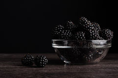 Fresh Ripe Juicy Blackberries in a plate on black background.  Stock Image