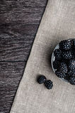 Fresh Ripe Juicy Blackberries in a plate on black background.  Stock Photos