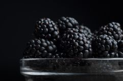Fresh Ripe Juicy Blackberries in a plate on black background.  Stock Images