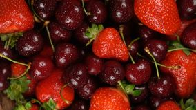Fresh, ripe, juicy cherries and strawberries background, close up berry, rotation loopable. Food background. Gastronomy. Fresh, ripe, juicy cherries and stock footage