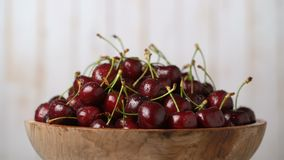 Fresh, ripe, juicy cherries in a wooden bowl, rotation loopable. Food background. Gastronomy concept, organic food. Fresh, ripe, juicy cherries in a wooden bowl stock footage