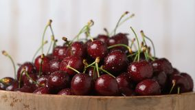 Fresh, ripe, juicy cherries in a wooden bowl, rotation zoom in. Food background. Gastronomy concept, organic food stock video