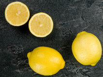 Fresh Ripe Juicy Citrus Lemons. Against a Black Textured Tile royalty free stock images