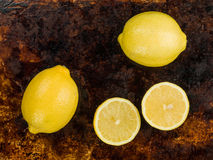 Fresh Ripe Juicy Citrus Lemons. Against a Distressed Oven or Baking Tray royalty free stock images