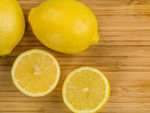 Fresh Ripe Juicy Citrus Lemons. Against a Wooden Kitchen Chopping Board stock image