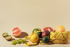 Fresh ripe juicy fruits and string bag on brown royalty free stock photography