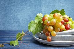 Fresh ripe juicy grapes in dishware on table. Against color background with space for text stock photography