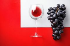 Fresh ripe juicy grapes, glass with red wine and space for text on color background. Top view royalty free stock photo