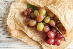 Fresh ripe juicy grapes and paper on table. Top view stock photo
