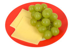 Fresh Ripe Juicy Green Grapes with Cheese Slices Healthy Vegetarian Snack. On a plate isolated white background Royalty Free Stock Photos