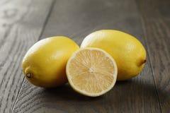 Fresh ripe lemons on old oak table Stock Photos