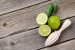 Fresh ripe limes and juicer Royalty Free Stock Images