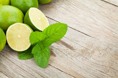 Fresh ripe limes with mint. On wooden table with copy space royalty free stock photos