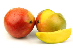 Fresh and ripe mango fruit and a cut one Stock Images