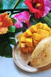 Fresh Ripe Mango on Wooden Plate. Close up fresh ripe mango serve on wooden plate with tropical flowers on background stock photos