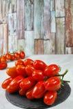 Fresh ripe mini roma tomatoes on grey board. And multicolored background Stock Photos