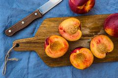 Fresh ripe nectarines, halved, whole on wood cutting board, knife, on blue table cloth, top view, close up, vibrant colors Royalty Free Stock Photos