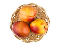Fresh ripe nectarines in wicker basket isolated on white Stock Photos