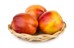 Fresh ripe nectarines in wicker basket on white Royalty Free Stock Photo