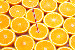 Fresh ripe oranges halved, background. Fresh ripe oranges halved, with drinking straw, background Stock Images
