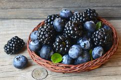 Fresh ripe organic blackberries and blueberries in a basket on old wooden table.Healthy eating,vegan food or diet concept. Selective focus royalty free stock image