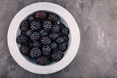 Fresh ripe organic blackberries in a bowl on a wooden background. Fresh ripe organic blackberries in a bowl on a wooden rustic background Stock Photos