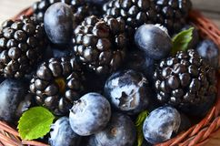 Fresh ripe organic blueberries and blackberries in a basket on old wooden table close up.Healthy eating,vegan food or diet concept. Selective focus stock image