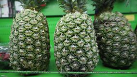 Fresh ripe organic pineapples are sold on the shelf in the local vegetable market. 4k resolution stock footage