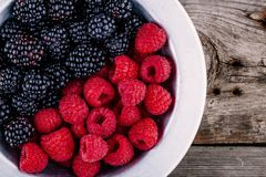 Fresh ripe organic raspberries and blackberries closeup in a bowl on a wooden background. Fresh ripe organic raspberries and blackberries in a bowl on a wooden Stock Images
