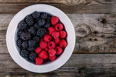 Fresh ripe organic raspberries and blackberries in a bowl on a wooden background. Fresh ripe organic raspberries and blackberries in a bowl on a wooden rustic Royalty Free Stock Photo