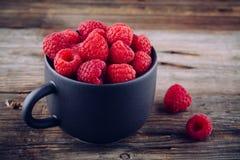 Fresh ripe organic raspberry in a mug on a wooden background. Fresh ripe organic raspberries in a mug on a wooden background Stock Photography