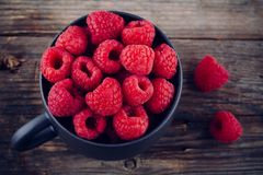 Fresh ripe organic raspberry in a mug on a wooden background Stock Photography