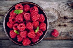 Fresh ripe organic raspberry in a plate on a wooden background Stock Photography