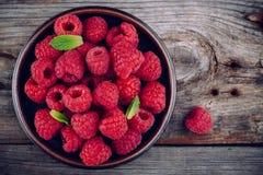 Fresh ripe organic raspberry in a plate on a wooden background. Fresh ripe organic raspberries in a plate on a wooden background Stock Photography
