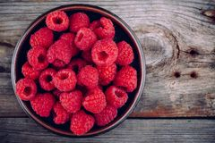 Fresh ripe organic raspberry in a plate on a wooden background Royalty Free Stock Photos