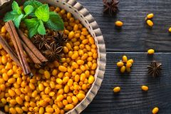Fresh ripe organic sea buckthorn berries in wooden bowl with cinnamon sticks, anise stars and mint on dark background. Stock Image