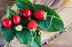 Fresh ripe organic strawberry and cherries on wooden background. Rustic style. Selective focus Royalty Free Stock Photo