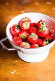 Fresh ripe organic strawberry in a white colander on a wooden table, selective focus. Harvest time. Raw berry. Organic and healthy. Food option. Healthy dessert Royalty Free Stock Images