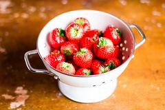 Fresh ripe organic strawberry in a white colander on a wooden table, selective focus. Harvest time. Raw berry. Organic and healthy. Food option. Healthy dessert Stock Photography