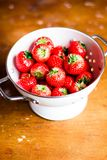 Fresh ripe organic strawberry in a white colander on a wooden table, selective focus. Harvest time. Raw berry. Organic and healthy. Food option. Healthy dessert Stock Image