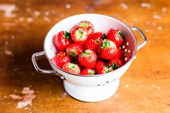 Fresh ripe organic strawberry in a white colander on a wooden table, selective focus. Harvest time. Raw berry. Organic and healthy. Food option. Healthy dessert Stock Photos