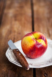 Fresh ripe peach on plate, wooden background Royalty Free Stock Images