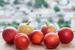 Fresh ripe peaches and apples on a city background Stock Photos