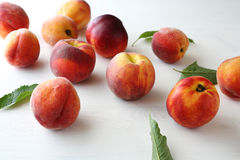 Fresh ripe peaches and leaves. On tablen Stock Photography