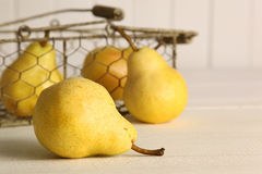 Fresh ripe pears in basket on table. Fresh ripe pears in metal basket on table Royalty Free Stock Photo