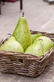 Fresh ripe pears in a wicker basket. Harvest of fresh ripe pears displayed in a wicker basket on a wall outdoors at a farmers market or for a quick delicious Royalty Free Stock Photography
